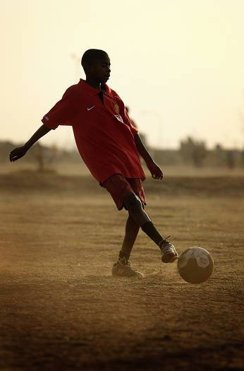 Young boys practise football in a public football ground wearing fake Manchester United merchandise. Kate Holt.