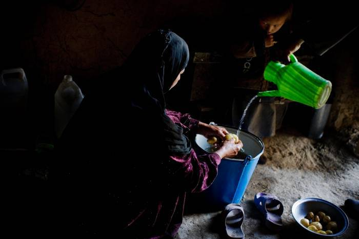 The wife of Yousef, who has six children, washes potatoes at their house. Kate Holt.