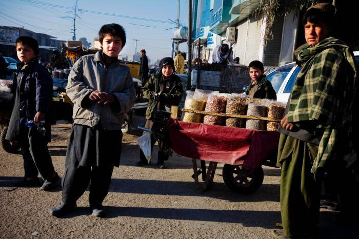 Young boys play in the street next to a vendor selling nuts in Lashkar Gah, Helmand, Afghanistan. Kate Holt.