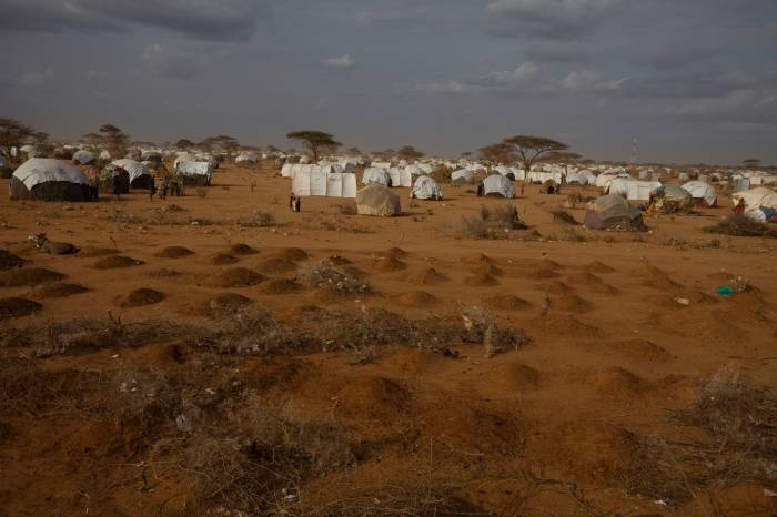 Small children stand next to a graveyard for newly arrived refugees from Somalia on the outskirts of Dagehaley camp. Kate Holt.