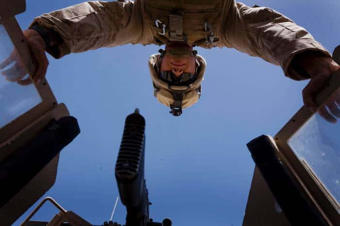 A US Marine looks down from his gunner post before starting a patrol in Mian Poshteh Helmand Province. Kate Holt.