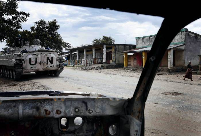A woman walks down and empty street passed a burnt out car and UN tank in Kiwanja. Kate Holt.