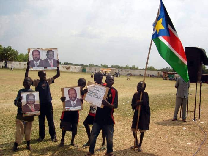 Street children hold photograph of the late Dr John Garang during a celebration of World Children's Day. Kate Holt.