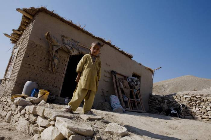 A young boy stands outside of his family's make shift house that they have lived in for a year. Kate Holt.