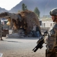 A soldier from the 82nd Airborne Division of the US army pass by the passes by a market stall. Kate Holt.