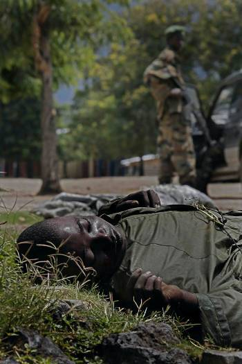 A rebel soldier looks towards a person who was killed the previous night, in Kiwanja. Kate Holt.