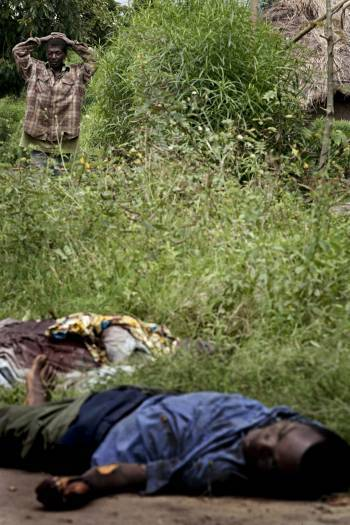 A man looks over two corpses, killed last night by rebel troops in Kiwanja. Kate Holt.