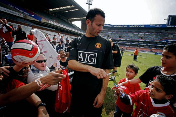 Ryan Giggs, Manchester United's longest serving player, autographs T Shirts for fans. Kate Holt.