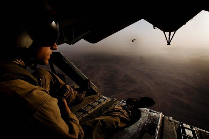 A US Marine looks out of the back of a transport helicopter. Kate Holt.