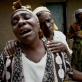Jane Kanyere is consoled by a neighbour after her son, Moise Kasereka , a teacher, was killed in fighting. Kate Holt.