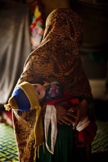 Gulmana's daughter holds her baby at their family's shelter in Jalalabad, Afghanistan. Kate Holt.