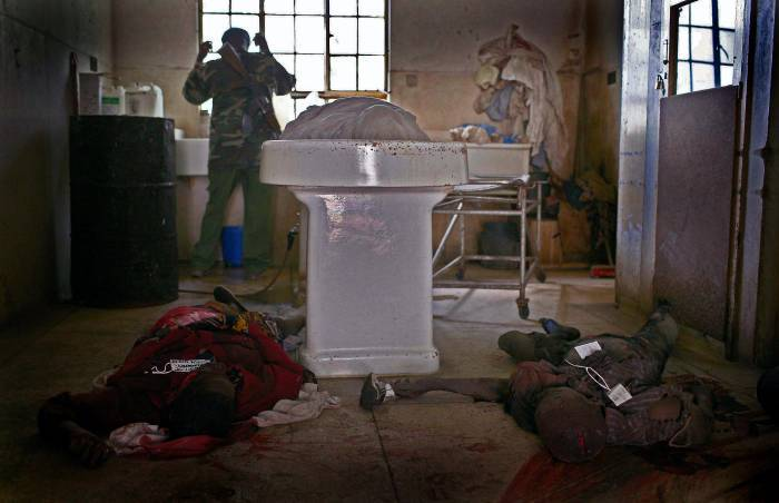 A soldier washes his hands after unloading dead bodies at the City mortuary in Nakuru. Kate Holt.
