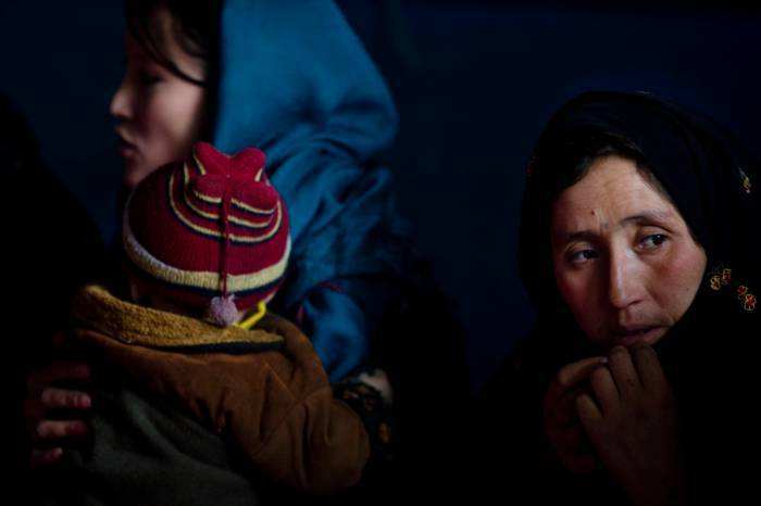 A woman holds her child who is suffering from acute diarrhea in the district hospital in Panjob. Kate Holt.