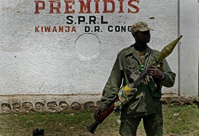 A rebel soldier, loyal to renegade General Laurent Nkuna, stands on guard in Kiwanja after a night of fighting. Kate Holt.