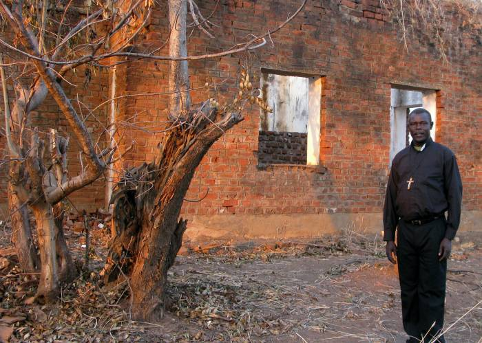 Father Oliver Nyara stands in front of St.Joseph the Worker Parish Church that was destroyed. Kate Holt.
