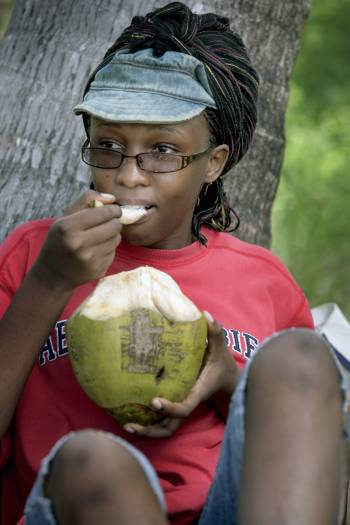 Gladys Luvuno Ndegwa an Earthwatch volunteer from Kenya enjoys eating a fresh coconut. Kate Holt.