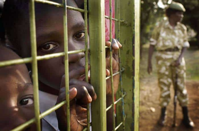 Children wait behind a gate, that is being guarded by armed wardens from the Kenyan Wildlife Service. Kate Holt.