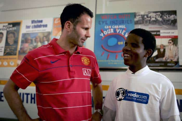 Ryan Giggs from Manchester United, talks to Richard, a blind boy. Kate Holt.