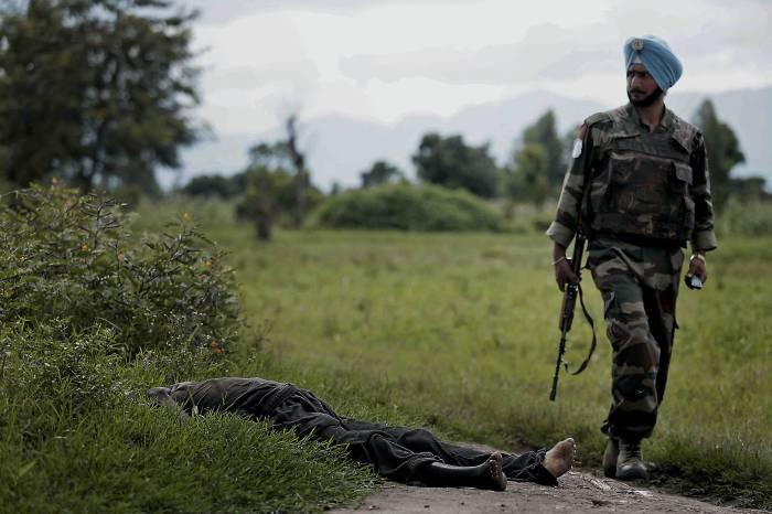 A UN peacekeeper from India walks past a dead body killed last night in Rutshuru. Kate Holt.