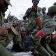 A bleeding Congolese man cuffed by Congolese government troops (FARDC) is taken away with 25 others. Kate Holt.