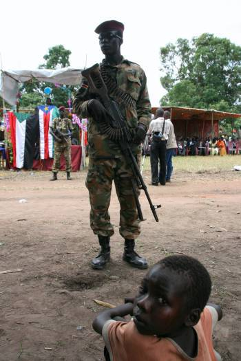 A young boy sits in front of an SPLA soldier at a celebration to mark the opening of Mundri Bridge. Kate Holt.