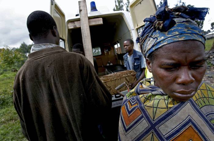 Wimana Ruhuwreru waits for the coffin of her son Emmanuel to be unloaded for burial in Goma. Kate Holt.