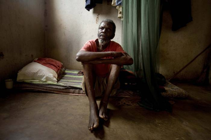 An elderly resident who is blind sits on his bed, at an elderly people's home. Kate Holt.