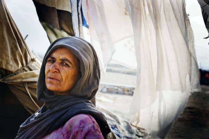 Kochay Serba poses for a photograph outside her shelter that her family have been living in. Kate Holt.