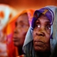 An elderly woman listens to Mia Farrow talk about the polio eradication at a community meeting. Kate Holt.