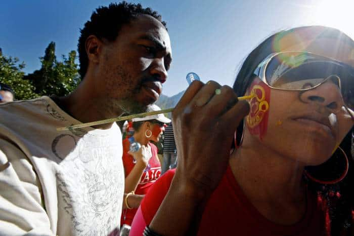 A face painter paints Manchester United logos onto fans faces before the opening game. Kate Holt.