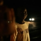 A young street boy is seen in the headlights of a passing car in a market place in Juba. Kate Holt.