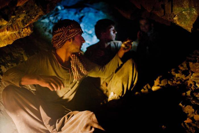 Azrat Mohammed looks passed a colleague while in a tunnel in which they mine emeralds in Khenj. Kate Holt.