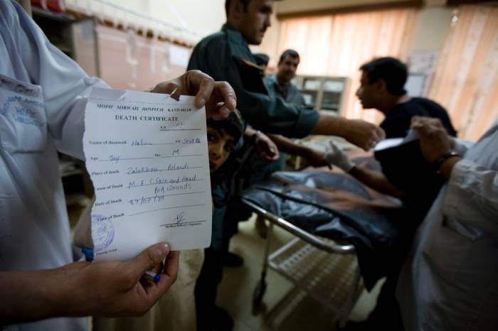 """A medic holds up a death certificate on which is written the cause of death as """"Big Wounds"""" in an OPD room. Kate Holt."""