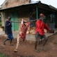 Two men carry meat in a traditional manner in the town of Mundri. Kate Holt.