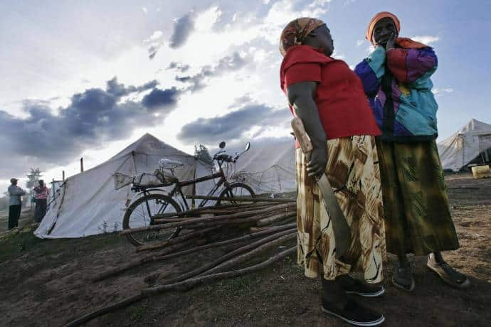 Two women talk about the day's events in a camp for displaced people in Mau Summit, Molo, Kenya. Kate Holt.