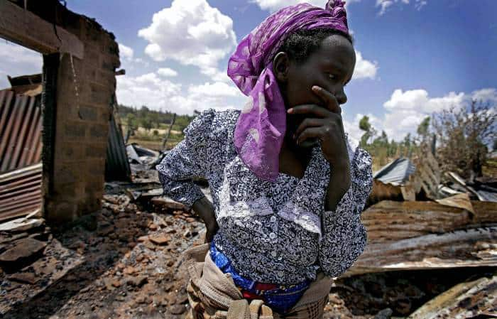 A Kikuyu woman surveys what remains of her house after it was burnt down. Kate Holt.