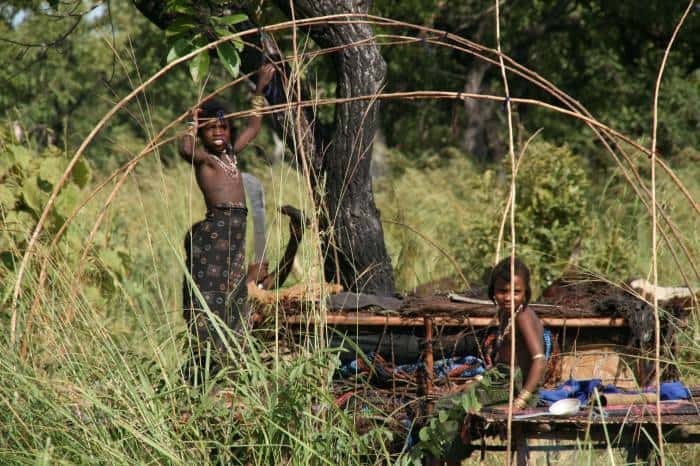 Young Ambororo girls build a traditional shelter at the side of river Ayii near village Bari. Kate Holt.