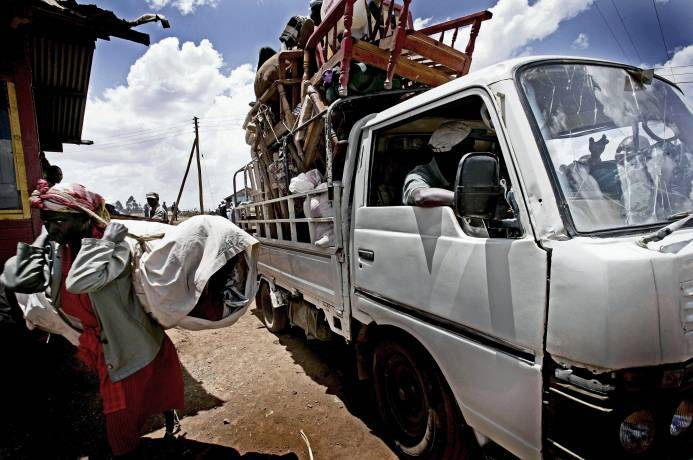 A Kikuyu woman flees with her belongings, alongside a truck piled high with furniture. Kate Holt.