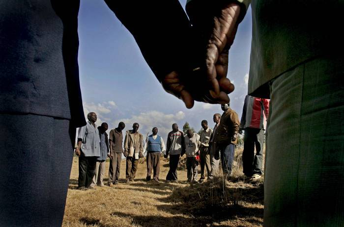 A group of Kikuyu and Kalinjen elders pray together after an emergency community meeting. Kate Holt.