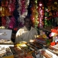 A man sits in his shop that is selling Christmas Decorations in Custom Market. Kate Holt.