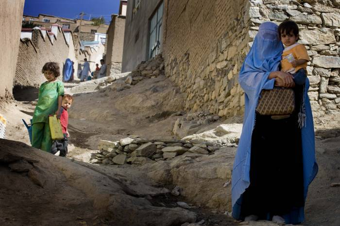 Mallalei Nafesa and her youngest daughter walk down the hill from their house in Sector 3, Kabul. Kate Holt.