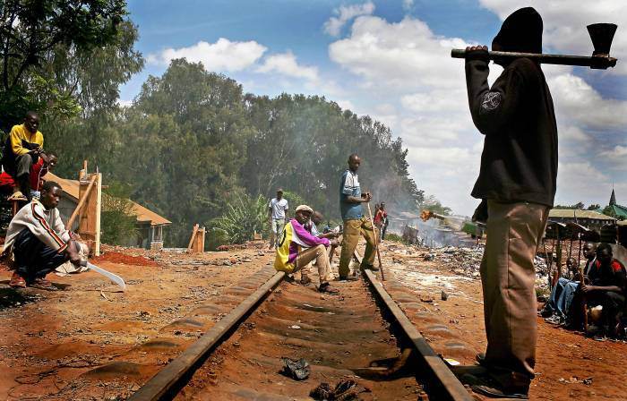 Young men from the Luo tribe wait on the railway line in Kibera slum. Kate Holt.