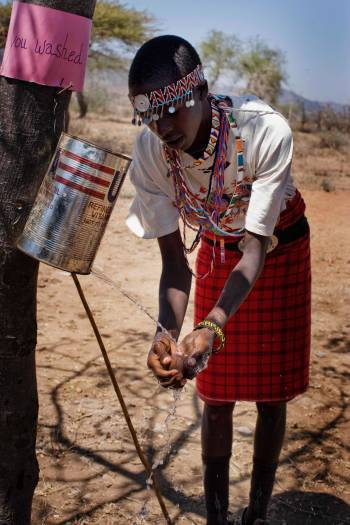 A pupil demonstrates the use of a leaky tin to wash their hands and face. Kate Holt.