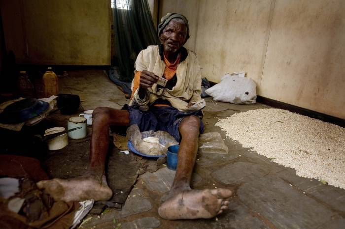 Sekwerekwe Bitoni sits on the floor of his home, that is a disused railway carriage. Kate Holt.