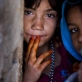 A young girl whose family have been displaced by recent fighting in Helmand poses for a photograph. Kate Holt.