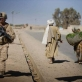 A US Marine walks passed a man with his donkey carrying wheat while out on patrol in Garmsir Helmand Province. Kate Holt.
