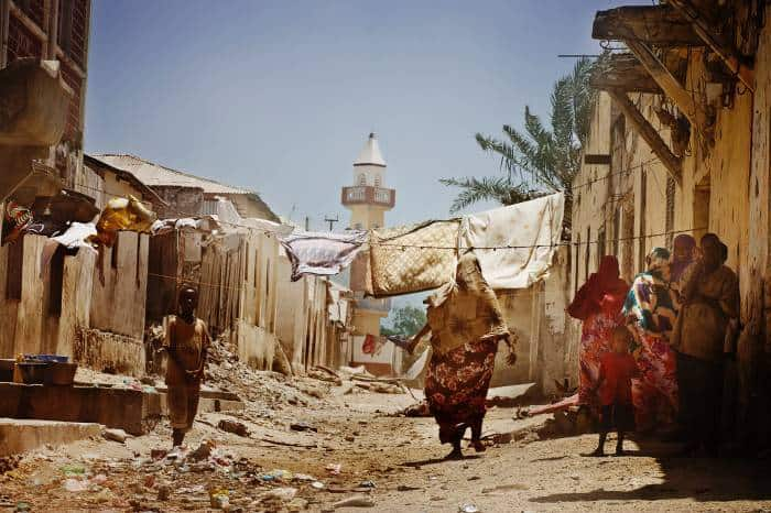 Women and children stand in a street that has recently been seized by AMISOM troops. Kate Holt.
