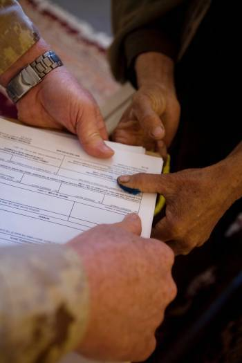 An elderly Afghan man puts his thumb print on a form to claim compensation for damage done to his property. Kate Holt.