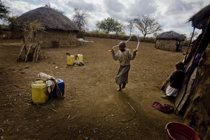Baby Larumbe, a young Masai girl, skips with her cousins in her family's compound. Kate Holt.