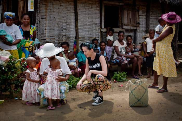 Katy Perry talks to twin girls while on a visit to a nutritional centre in the village Androranga Vola. Kate Holt.